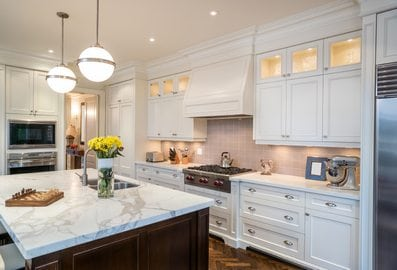 Under cabinet LEDs as well as inside cabinet lighting brighten this contemporary kitchen